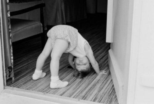 Posterazzi SAL255424399 Little Girl Exercising in Doorway Poster Print - 18 x 24 in.